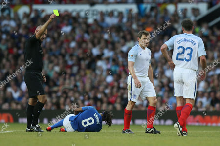 Ben Shephard is booked by referee Howard Webb for a foul on Edgar Davids during the Soccer Aid match between England XI and the Rest of the World XI played at Old Trafford, Manchester on June 5th 2016