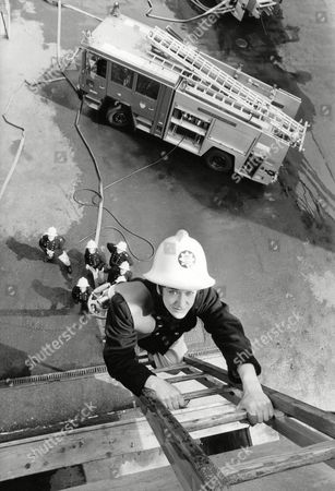 Stock Picture of Tv Programme: London's Burning. Actress Katharine Rogers Climbing A Fireman's Ladder. Box 650 304121564 A.jpg.