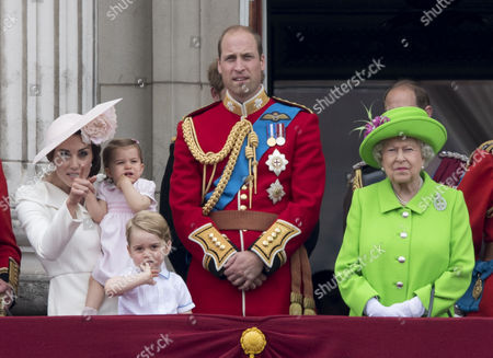 Catherine Duchess of Cambridge, Princess Charlotte of Cambridge, Prince George, Prince William and Queen Elizabeth II watch the flypast from the balcony of Buckingaham Palace