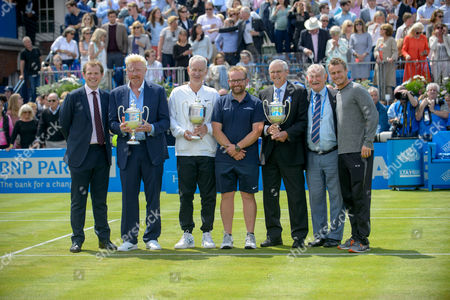 Stock Photo of On court presentation of replica trophies to players who have won Queens four times. [L-R] Stephen Farrow [Tournament Director], Boris Becker, John McEnroe, Graham Kimpton [Head Groundsman Queens Club] Roy Emerson, Jim Moore [Tournament Referee], Lleyton Hewitt.   Aegon Tennis Championships, The Queens Club, London,  Britain. 17th June 2016.