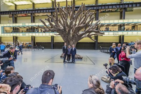 Sir Nicholas Serota, Lord John Browne, Frances Morris in the Turbine Hall with Ai Weiwei's 7-metre high sculpture of a tree