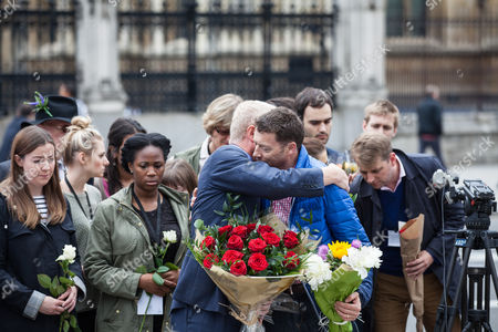 John Cryer MP (left), Chair of the Parliamentary Labour Party, and Iain McNicol (right), General Secretary of the Labour Party, share a hug as they lay flowers in Parliament Square in tribute to Jo Cox MP, who died on 16 June 2016 after being shot and stabbed in Birstall, Leeds.