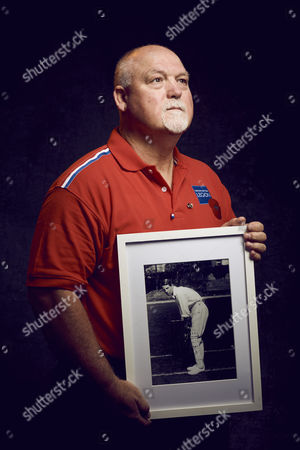 Mike Gatting OBE, former England cricket captain and Middlesex batsman holding a picture of Lt Kenneth Lotherington Hutchings