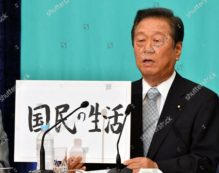 Ichiro Ozawa of Peples Life Party holds a hand-written slogan for the upcoming House of Councillors election