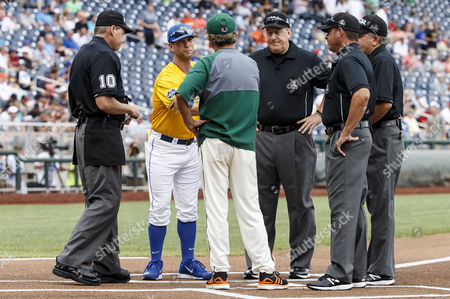 Miami head coach Jim Morris and UC Santa Barbara head coach Andrew Checketts meet with game umpires to exchange lineup cards before game 5 of the NCAA Men's College World Series between Miami Hurricanes and UC Santa Barbara Gauchos at TD Ameritrade Park in Omaha, NE