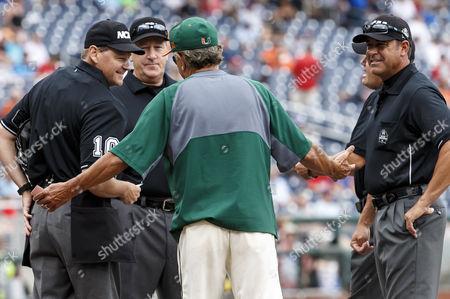 Miami head coach Jim Morris jokes with umpires before game 5 of the NCAA Men's College World Series between Miami Hurricanes and UC Santa Barbara Gauchos at TD Ameritrade Park in Omaha, NE