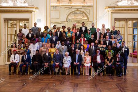 Stock Image of Queen Elizabeth II and Prince Harry sit for a group photo with guests David Beckham and Sir John Major and the sixty winners of the Queen's Young Leaders Awards at Buckingham Palace in London. Front row left to right: David Morfaw (Cameroon), Asante Mzungu (Malawi), Olumide Femi Makanjuola (Nigeria), David Beckham, Prince Harry, Queen Elizabeth II, Sir John Major, Annabelle Xerri (Malta), Jacob Thomas (Australia), Seini Fisi'ihoi (Papua New Guinea), Kartik Sawhney (India). Second row: Kelly Lovell (Canada), Moitshepi Matsheng (Botswana), Rachel Nungu (Tanzania), Matetsabisa Molapo (Lesotho), Olanrewaju Adeloye (Nigeria), Jessica Dewhurst (South Africa), Deidra Smith, (Belize), Trevis Belle (Saint Kitts & Nevis), Calvin Woo Yoong Shen (Malaysia), Katerina Gavrielidou (Cyprus), Alexander Stonyer-Dubinovsky (Australia), Valentino Wichman (New Zealand), Easter Tekafa Niko (Tuvalu), Safaath Ahmed Zahir (Maldives), Mary Siro (Vanuatu). Third row: Christina Giwe (Papua New Guinea), Susan Mueni Waita (Kenya), Imrana Alhaji Buba (Nigeria), Lethabo Ashleigh Letube (South Africa), Firhaana Bulbulia (Barbados), Tijani Christian (Jamaica), Neha Swain (India), Nushelle de Silva (Sri Lanka), Ella Mckenzie (UK), Brad Olsen (New Zealand), Aiona Prescott (Tonga). Fourth Row: Akzima Elisha Bano (Fiji), Peris Bosire (Kenya), Drucila Meireles (Mozambique), Howard Nelson-Williams (Sierra Leone), Shamelle Rice (Barbados), Ali Dowden (Grenada), Osama Bin Noor (Bangladesh), Mark Jin Quan Cheng (Singapore), Ashleigh Porter-Exley (UK), Unique Harris (Nauru). Fifth row: Anayah Phares (Canada), Alex Mativo (Kenya), Deegesh Maywah (Mauritius), Angelique Pouponneau (Seychelles), Regis Burton (Antigua & Barbuda), Tina Alfred (Dominica), Dillon Ollivierre (Saint Vincent & the Grenadines), Zainab Bibi (Pakistan), Adam Bradford, (UK), Tabotabo Auatabu (Kiribati), Nolan Salmon Parairua (Solomon Islands). Back row: Oladipupo Ajiroba (Nigeria), Paul-Miki Akpablie (Ghana), Madalo Timur Yun