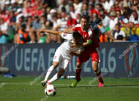 Stephan Lichtsteiner of Switzerland battles with Slawomir Peszko of Poland    during the UEFA Euro 2016  Round of 16 match between Switzerland and  Poland   played at Stadium Geoffroy Guichard , Saint-Etienne , France on June 25th  2016