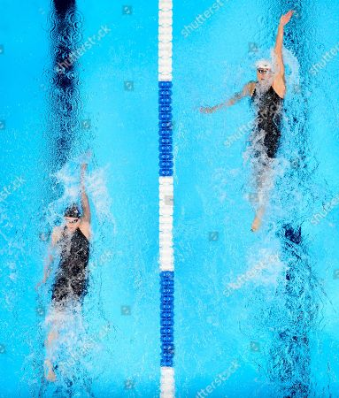 Natalie Coughlin, right, leads Claire Adams during their heat in the women's 100 metre backstroke preliminaries at the U.S. Olympic swimming trials
