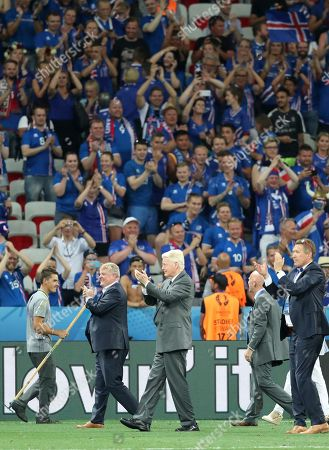 Iceland President Olafur Ragnar Grimsson, center, applauds on the pitch at the end of the match