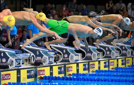 Tyler Clary, center, dives at the start of a preliminary heat in the Men's 400 metre individual medley