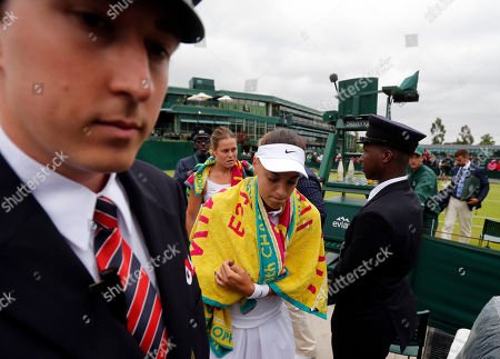 Ana Konjuh of Croatia, front, and Karin Knapp of Italy leave the court during rain on day three