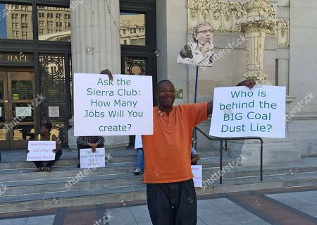 Stevie Johnson holds up a pair of signs during a protest outside City Hall before a scheduled vote