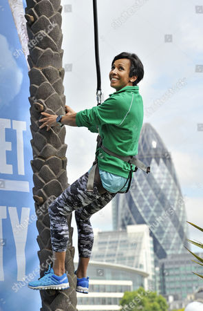 Stock Image of Dame Kelly Holmes brings the sunshine to London and works up a thirst shimmying up a huge 23ft coconut tree at the Vita Coco Coconut Grove in Potters Fields Park, London. The stunning tropical beach hangout is open to all, and Londoners are being encouraged to come down and see if they can match - or even beat - Dame Kelly's time of 6.7 seconds, for the chance of winning an adventurous fun-filled trip.