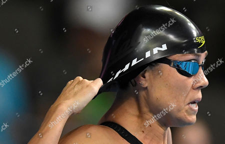 Natalie Coughlin adjusts her cap before the start of her heat in the women's 100 metres freestyle preliminaries