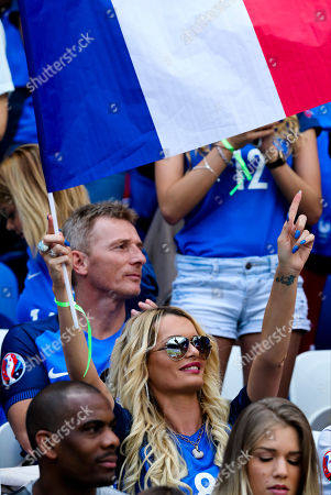 Ludivine Payet, wife of France's Dimitri Payet, waves a French flag on the stands during the Euro 2016 round of 16 soccer match between France and Ireland, at the Grand Stade in Decines-­Charpieu, near Lyon, France