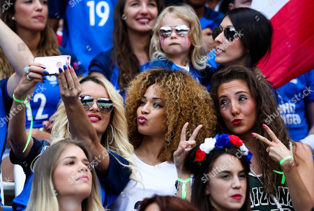 Ludivine Payet, left, wife of France's Dimitri Payet, poses for a photo with others on the stands during the Euro 2016 round of 16 soccer match between France and Ireland, at the Grand Stade in Decines-­Charpieu, near Lyon, France