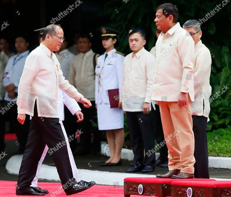 New Philippine President Rodrigo Duterte, right, stands on the dais as outgoing President Benigno Aquino III reviews the troops during inauguration ceremony at Malacanang Palace grounds in Manila