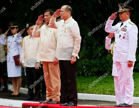 New Philippine President Rodrigo Duterte, left, and outgoing President Benigno Aquino III salute during the inauguration ceremony at Malacanang Palace grounds in Manila
