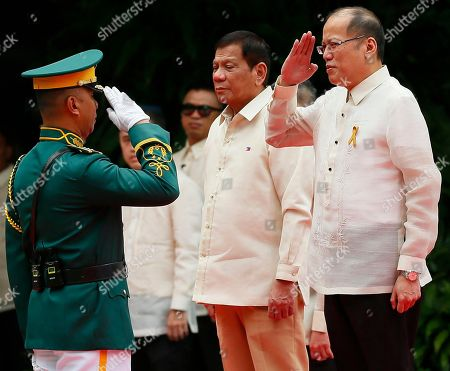 New Philippine President Rodrigo Duterte, center, stands at attention as outgoing President Benigno Aquino III salutes the troop commander during inauguration ceremony at Malacanang Palace grounds in Manila