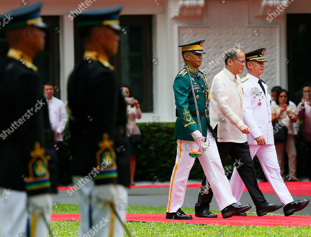 Outgoing President Benigno Aquino III, second from right, reviews the troops for the last time during inauguration ceremony for new Philippine President Rodrigo Duterte at Malacanang Palace grounds in Manila