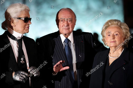 German fashion designer Karl Lagerfeld, left, Ritz owner Mohamed Al-Fayed and Bernadette Chirac, wife of former French President Jacques Chirac, pose for a photograph, Monday, June 27, 2016. Ritz hotel owner Al Fayed and officials from Paris City Hall and the French government are inaugurating the newly renovated column at Place Vendome. Al Fayed funded the restoration of the column as a gift to the city, and his hotel recently reopened after years of renovations