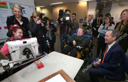 Australia's opposition Labor Party leader Bill Shorten, seated right, and deputy Labor leader Tanya Plibersek, second left, meet with members of a disability center in Sydney, Friday, July 1, 2016. Shorten is campaigning on the last day before a national election.
