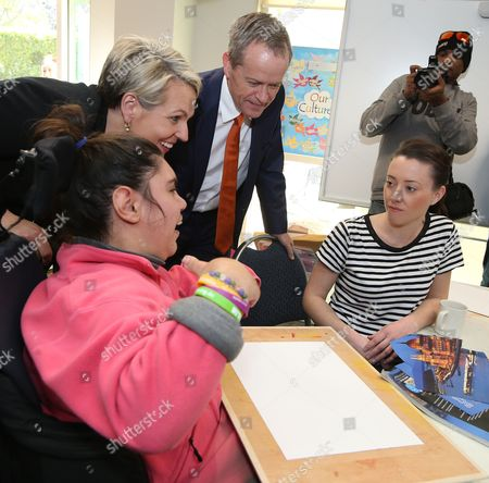 Australia's opposition Labor Party leader Bill Shorten, center, and deputy Labor leader Tanya Plibersek, second left, meet with members of a disability center in Sydney, Friday, July 1, 2016. Shorten is campaigning on the last day before a national election.