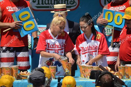 Women's defending champion Miki Sudo (left) wins the women's contest by eating 38.5 hot dogs in 10 minutes. Sonya Thomas (right) places second by eating 35 hot dogs.