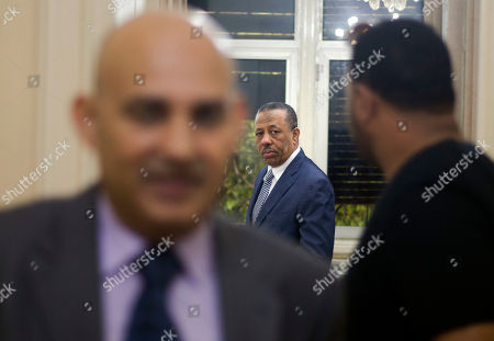 Libyan Prime Minister Abdullah al-Thinni, center, is surrounded by embassy officials as he prepares to enter a room for an interview with the Associated Press at the Libyan embassy in Cairo, Egypt, Tuesday, July 5, 2016. Al-Thinni of the interim government based in the eastern region, told The Associated Press on Wednesday that the UN-brokered deal has so far backfired, deepened rift and reached a deadlock. The deal must be amended, he said.