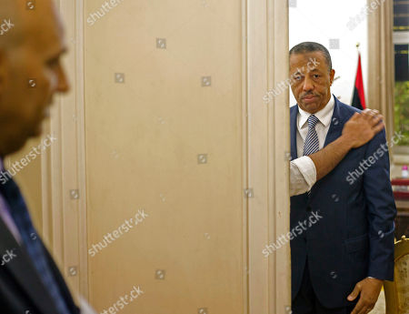 An assistant adjusts Libyan Prime Minister Abdullah al-Thinni, as he prepares to enter a room for an interview with the Associated Press at the Libyan embassy in Cairo, Egypt, Tuesday, July 5, 2016. Al-Thinni of the interim government based in the eastern region, told The Associated Press on Wednesday that the UN-brokered deal has so far backfired, deepened rift and reached a deadlock. The deal must be amended, he said.