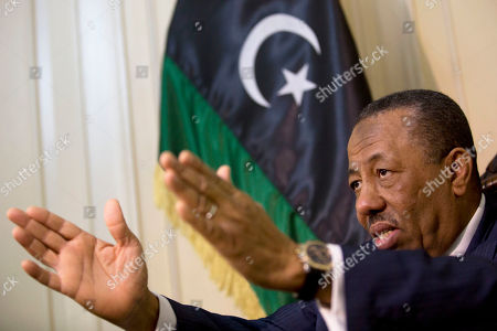 Stock Picture of Libyan Prime Minister Abdullah al-Thinni, speaks during an interview with the Associated Press at the Libyan embassy in Cairo, Egypt, Tuesday, July 5, 2016. Al-Thinni of the interim government based in the eastern region, told The Associated Press that the UN-brokered deal has reached a deadlock. The deal must be amended, he said. Libyan flag seen at background.