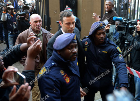 Police escort Oscar Pistorius in before his sentencing at the Northern Gauteng High Court, Pistorius was sentenced to six years in prison for the murder of his girlfriend, Reeva Steenkamp