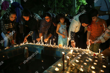 "Iranians light candles in a candlelit ceremony at Cinema Museum in Tehran, Iran, Tuesday July 5, 2016, to mourn the death of film director Abbas Kiarostami, who died at the age of 76 after a career spanning more than four decades. Kiarostami wrote and directed dozens of films, and his 1997 film ""Taste of Cherry"" won the prestigious Palme d'Or at the Cannes Film Festival. He died in Paris, where he was undergoing treatment for cancer."