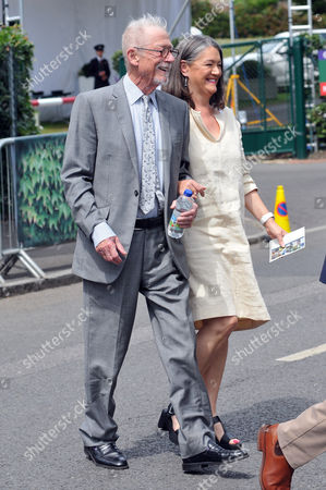 Sir John Hurt with his wife Anwen arrives for the ladies singles final.