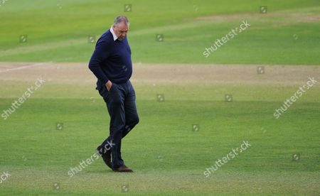 Angus Fraser, Middlesex managing Director for cricket looks at the pitch.