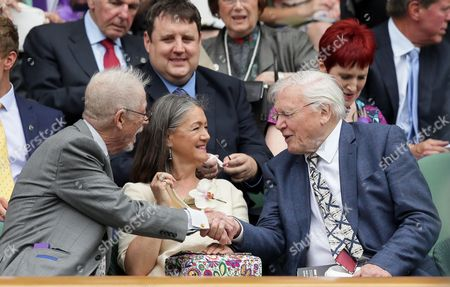 Actor John Hurt, left, next to his wife Anwen Rees-Myers, greets David Attenborough in the Royal Box on day thirteen of the Wimbledon Tennis Championships in London