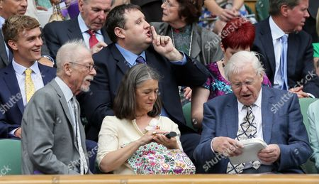 Actor John Hurt, left, next to his wife Anwen Rees-Myers, speaks with David Attenborough in the Royal Box on day thirteen of the Wimbledon Tennis Championships in London