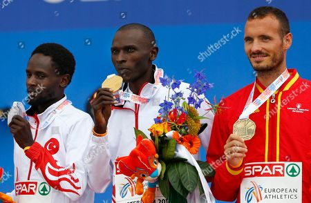 Turkey's gold medal winner Polat Kemboi Arikan is flanked by Turkey's silver medal winner Ali Kaya and Spain's bronze medal winner Antonio Abadia during the ceremony for the men's 10,000m at the European Athletics Championships in Amsterdam, the Netherlands