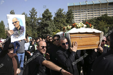A group of Iranian film assistant directors carry the coffin of director Abbas Kiarostami as a woman holds a poster showing him at his funeral ceremony in Tehran, Iran