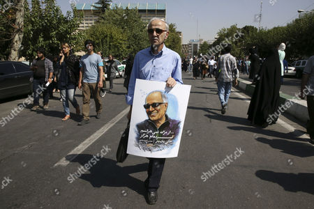 A man holds a poster of Iranian film director Abbas Kiarostami at his funeral ceremony in Tehran, Iran