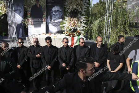 Mourners attend funeral ceremony of film director Abbas Kiarostami while his coffin is placed at background, in Tehran, Iran