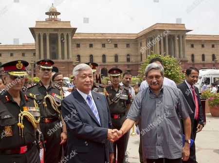 India's Defense Minister Manohar Parrikar, right, shakes hands with his Japanese counterpart Gen Nakatani upon his arrival at the India Defense Ministry in New Delhi