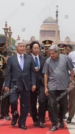 India's Defense Minister Manohar Parrikar, right, talks with his Japanese counterpart Gen Nakatani, left, upon his arrival at the India's Defense Ministry in New Delhi