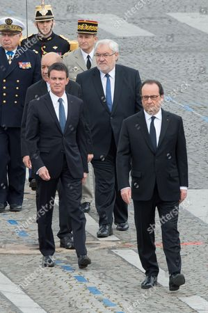 French President Francois Hollande (L), French Defence minister Jean-Yves Le Drian (back, L), French Prime minister Manuel Valls (2ndR) and French junior minister for Veterans Jean-Marc Todeschini arrive for the annual Bastille Day military parade on the Champs-Elysees avenue in Paris