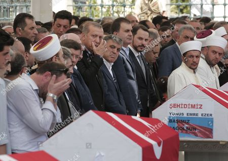 Mourners, including Turkey's President, Recep Tayyip Erdogan, and former president, Abdullah Gul, rear centre, offer their prayers during the funeral for people killed Friday while protesting the attempted coup against Turkey's government, in Istanbul. Rather than toppling Turkey's strongman president, a failed military coup appears to have bolstered Erdogan's immediate grip on power and boosted his popularity.