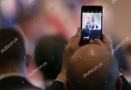 A guest holds up his phone as he records U.S. Vice President Joe Biden and New South Wales state Premier Mike Baird during a business roundtable at the Sydney Opera House in Sydney