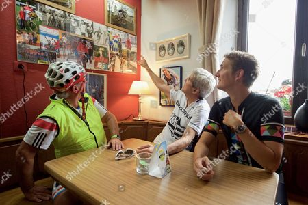 U.S. Secretary of State John Kerry, joined by Luxembourgian Foreign Minister Jean Asselborn and national biking hero Andy Schleck, looks at a photo on the wall in the Restaurant Relais Bausch in Brouch