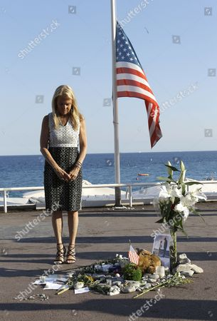 U.S Ambassador to France Jane D. Hartley pays tribute on the famed Promenade des Anglais, at a makeshift memorial in Nice, southern France