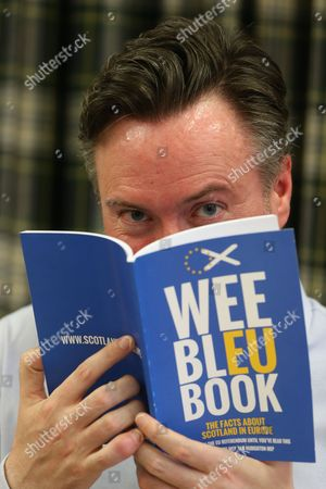 """Alyn Smith MEP (SNP) holds the """"Wee Bleu Book"""" he co-authored with fellow SNP MEP Ian Hudghton"""